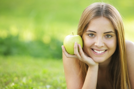 Young smiling woman outdoors holding an apple Stock Photo - 14620809