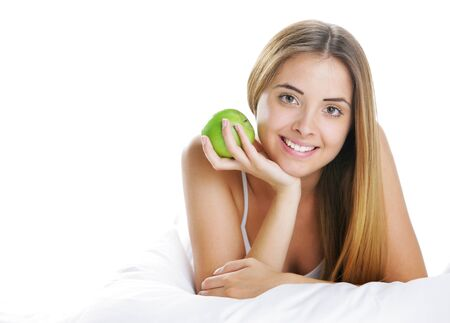 Smiling Young Woman Holding Apple in Bed photo