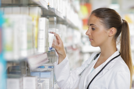 pharmacy store: Portrait of a young female pharmacist selecting a medication