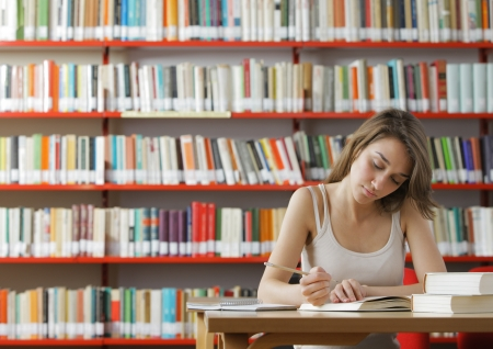Portrait of a serious young student reading a book in a library Stock Photo - 14676095