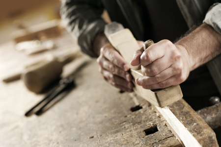 Hände eines Zimmermanns gehobeltes Holz, am Arbeitsplatz