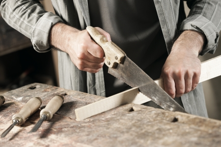 saws: Carpenter saws plank by handsaw Stock Photo