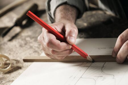 Closeup view of a carpenter using a red pencil to draw a line on a blueprint