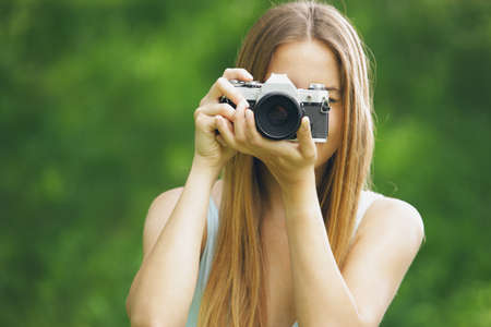 photographing: Young woman taking a picture with an old camera Stock Photo