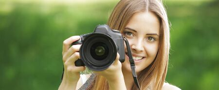 Portrait of beautiful smiling blonde girl , making photos at summer green park. photo