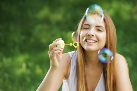 Beautiful young woman smiling and blowing bubbles outdoor in the nature. photo