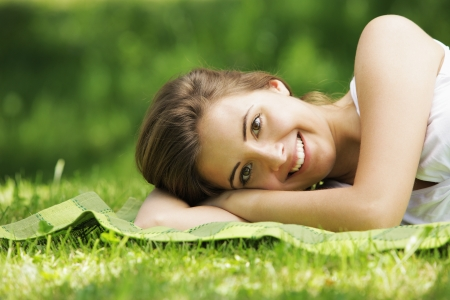 Young smiling woman laying on the grass  photo