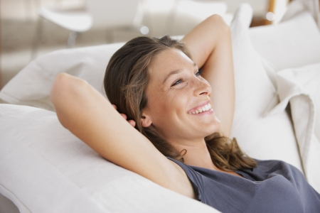 and relax: Closeup of a smiling young woman lying on couch Stock Photo