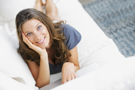 Pretty woman lying on sofa with laptop Stock Photo - 14882214