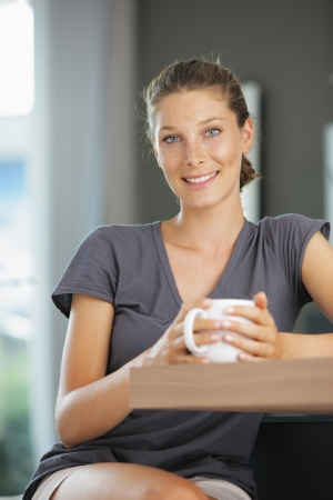 Young smiling woman sitting with a cup of coffee photo