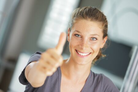 Portrait of beautiful young woman holding a thumbs up to the camera photo