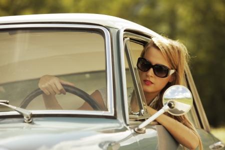 shades: Young woman driving vintage car.