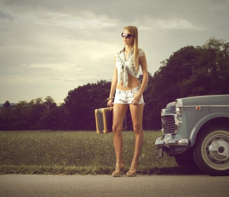 hitchhiking: Young sexy girl with suitcase and vintage cars