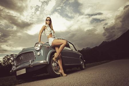 Mod�le de mode avec voitures anciennes, ciel nuageux sur fond photo