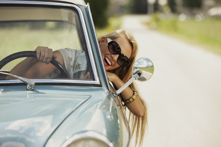 car driving: Smiling woman driving vintage car. Stock Photo