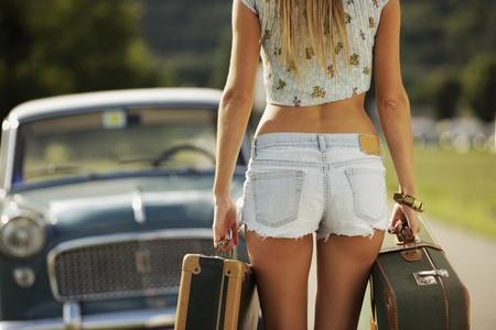 culo: Sexy chica con maletas, coches de época en el fondo Foto de archivo