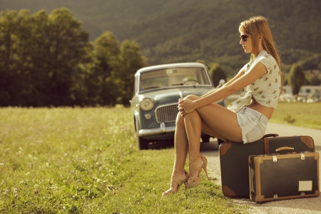waiting girl: Young sexy woman sitting on suitcases at the roadside, vintage cars in the background