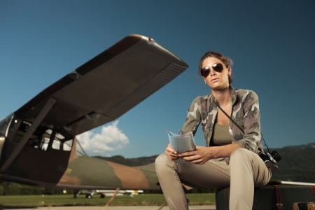 Beautiful young woman sitting on a suitcase at the airport. Airplane in the background photo