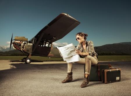 femme valise: Belle jeune femme assise sur une valise, se penche sur une carte. Avion en arrière-plan