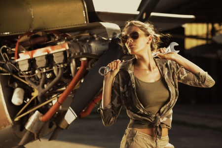 place of work: Woman airplane mechanic. Airplane on the background