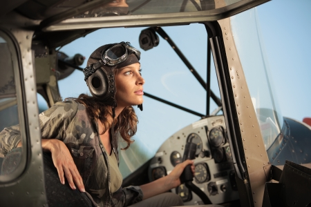 Portrait of young woman pilot in a military airplane photo