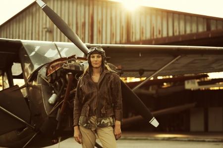 piloto: Retrato de mujer joven aviador, avi�n y el hangar en el fondo