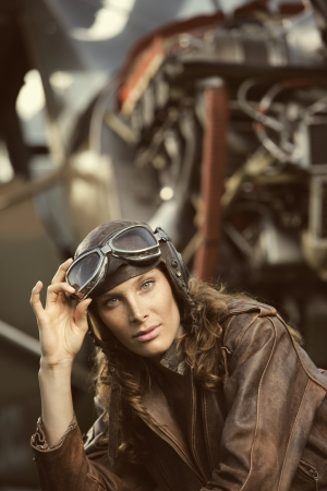 aviator: Portrait of young woman airplane pilot. Airplane on the background