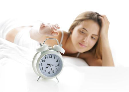 Woman turning off the alarm clock photo