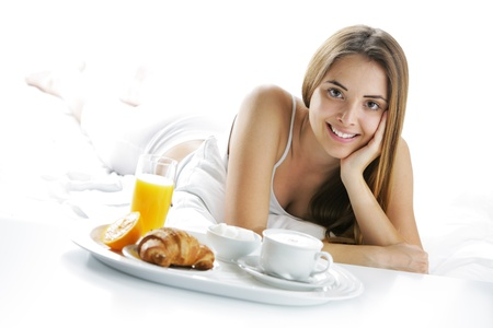 breakfast hotel: Young beautiful woman having breakfast in bed.