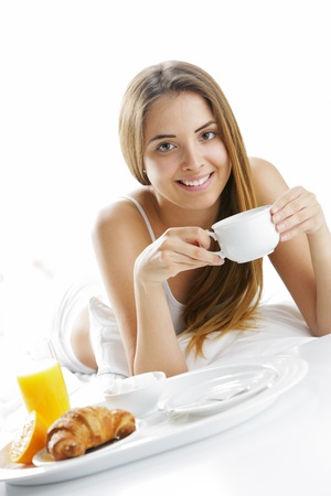 Young beautiful woman having breakfast in bed. photo