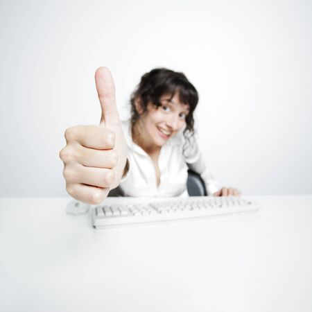 thumbs up shown by a happy, smiling young woman working at her office desk photo