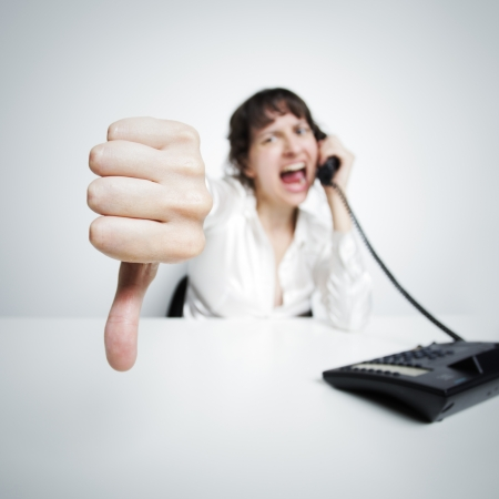 an hostile woman shows thumbs down against us (at the camera) while phoning at her office desk Stock Photo - 15037926