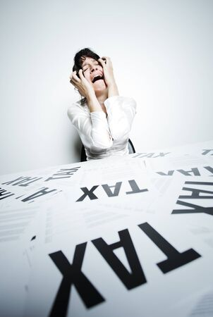 taxes budgeting: Desperate woman at her taxes-paperwork covered desk to crying bitter tears with her hands on face Stock Photo