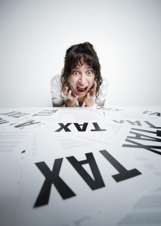 taxes: Sorprendido mujer mirando un mont�n de preocuparse formularios de impuestos en su escritorio