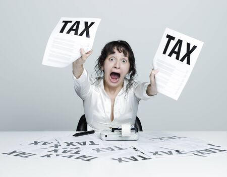 Young desperate woman at her desk showing terrible tax bills to the camera while shouting out photo