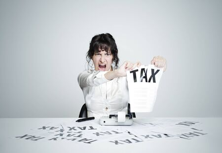 Young desperate woman at her paperwork-covered desk ripping up a tax form staring at the camera Stock Photo - 15037938