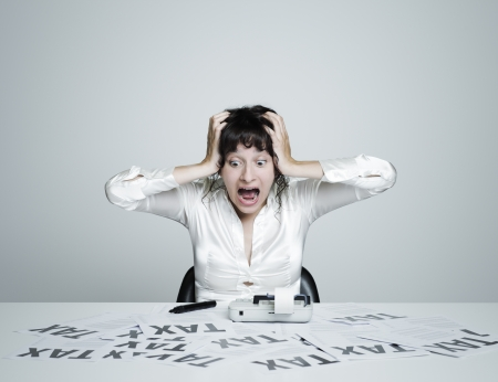 impuestos: Mujer joven sorprendida en su escritorio asustado por impuestos grita tomados de la mano en la cabeza