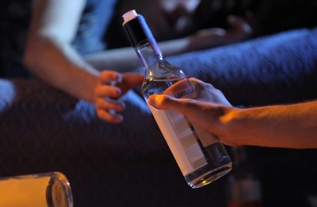jovenes tomando alcohol: Dos jóvenes se emborrachan en casa Foto de archivo