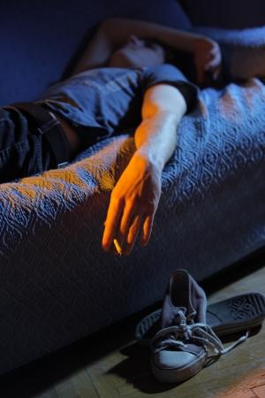 articulaciones: Hombre joven tumbado en el sof� fumando un porro Foto de archivo