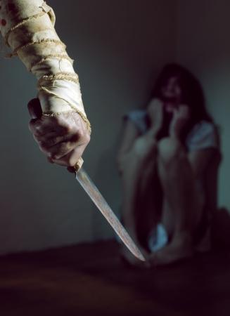 the knife: Asustada mujer amenazada por un hombre con un cuchillo ensangrentado Foto de archivo