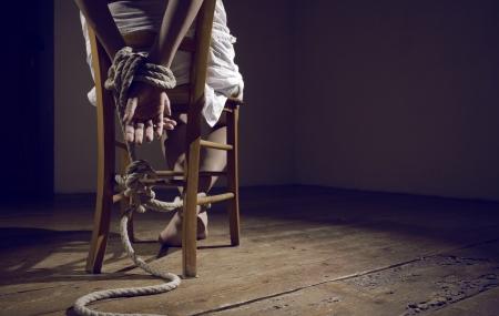 Junge Frau auf einem Stuhl in einem leeren Raum gebunden