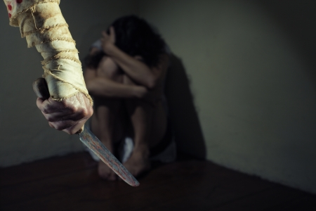 threatened: Scared woman threatened by a man with bloody knife