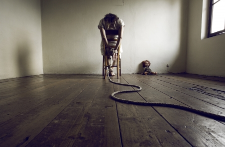 woman tied: Young woman tied to a chair in a empty room