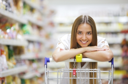 happy shopping: Happy blonde shopper smiles over supermarket shopping cart