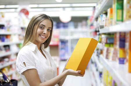 Woman checking food labelling in supermarket photo