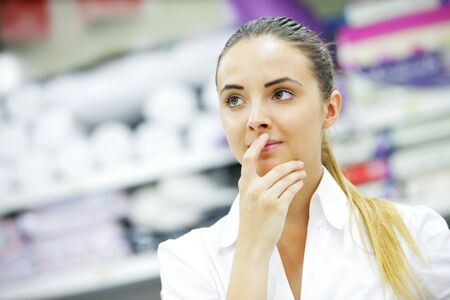 Beautiful blonde, hand to lips, chooses product in supermarket photo