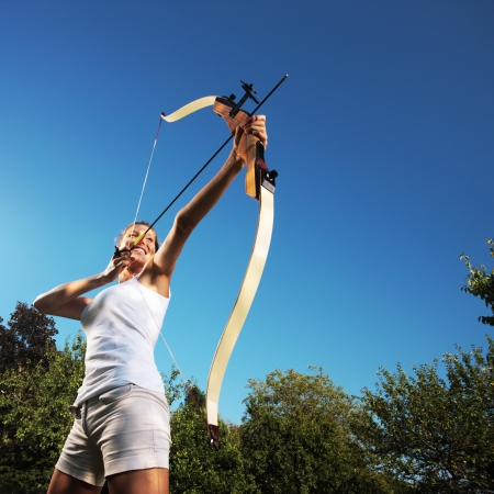 archer: Attractive woman bending a bow and aiming in the sky