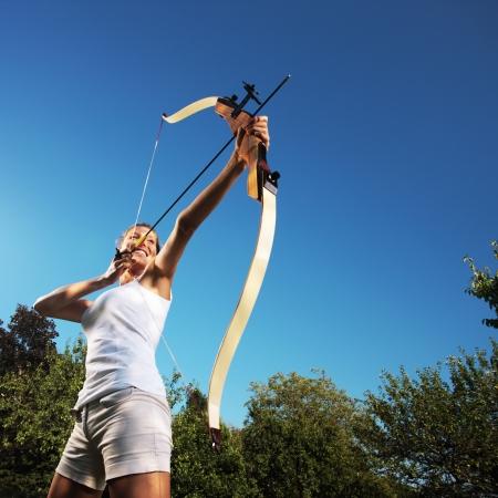 arco y flecha: Mujer atractiva doblar un arco y apuntar en el cielo