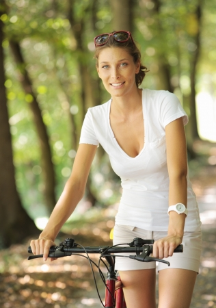 eye traveller: Young woman on a bicycle in the forest
