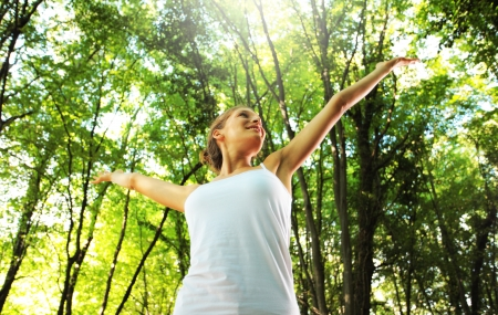 outstretched arms: Young beautiful woman arms raised enjoying the nature in green forest Stock Photo